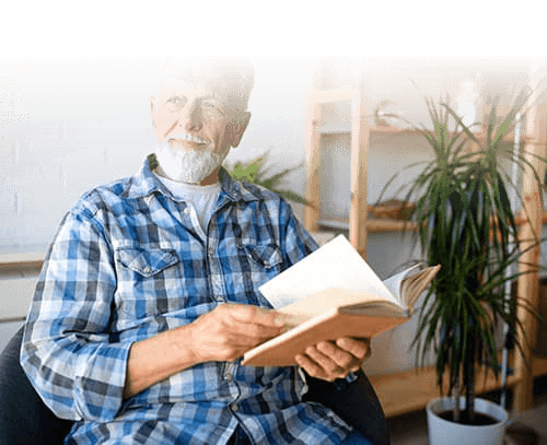 man reading a book at senior living facility